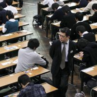 On the prowl: A proctor monitors an entrance exam session at the University of Tokyo's Hongo campus in Bunkyo Ward last month. | KYODO PHOTO