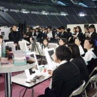Looking the part: Kao Corp. beauticians show college students how to apply makeup for job interviews during a job fair in Sapporo on Feb. 7. | KYODO PHOTO