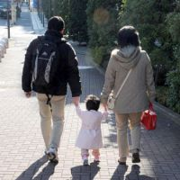 Family outing: Parents and their child stroll along a street in Minato Ward, Tokyo, in December.   SATOKO KAWASAKI PHOTO