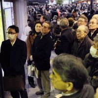 Left in limbo: Stranded passengers watch a TV at JR Shinbashi Station after Friday's big earthquake stopped railways in the Kanto region and northern Japan. | KYODO PHOTO