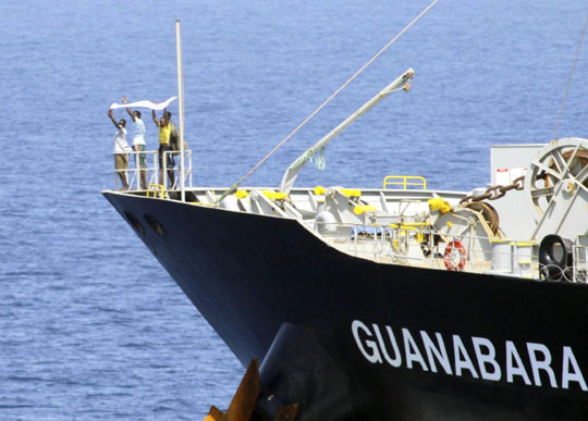 Game over: Suspected pirates signal their surrender to the U.S. Navy from the bow of the Japan-owned oil tanker the Guanabara in the Arabian Sea on Sunday. | AP/KYODO PHOTO