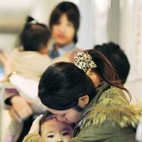 Stay close: A mother holds her child as aftershocks rattle a ward office in Sendai on Saturday. | KYODO PHOTO