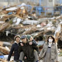 What's left: Residents of Miyagino Ward, Sendai, walk amid the ruins of their neighborhood Saturday morning as they evacuate to safer areas. | KYODO PHOTO