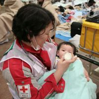 Lucky one: A baby who survived last Friday's mega-quake is fed milk by a member of the Japanese Red Cross National Disaster Response Team at Ishinomaki Red Cross Hospital in Ishinomaki on Saturday. The photo was provided by the Japanese Red Cross Society.   AP PHOTO