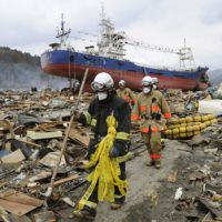 Where to begin: Firefighters search tsunami-devastated areas of Kesennuma, Miyagi Prefecture, on Tuesday as a big ship lies high and dry among the debris.   KYODO PHOTO
