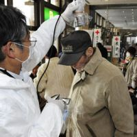 Reading the situation: An evacuee is checked for radiation at a shelter in the city of Fukushima on Thursday. | KYODO PHOTO