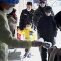 Waiting in line: A boy stands with others at an evacuation center in the city of Fukushima on Friday before being screened for radiation. | KYODO PHOTO