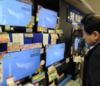 Safe distance: A man at an Osaka electronics store watches a Self-Defense Forces helicopter drop water on the No. 3 reactor at the Fukushima No. 1 nuclear power station Thursday.   KYODO PHOTO