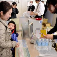 On the safe side: A mother with her baby receives bottled water Thursday at the Shibaura branch of the Minato Ward office in Tokyo amid public concern that tap water is contaminated with radioactive iodine.   YOSHIAKI MIURA PHOTO