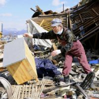 Altered landscape: A man tries to clear rubble Thursday in Ofunato, Iwate Prefecture, on the site where his tsunami-wrecked shop used to stand. | KYODO PHOTO