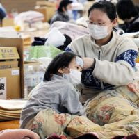 Tender loving care: A woman takes care of her daughter, who has a cold, at a shelter in the city of Fukushima on Thursday. They evacuated from Minamisoma, only 25 km from the Fukushima No. 1 nuclear plant.   KYODO PHOTO