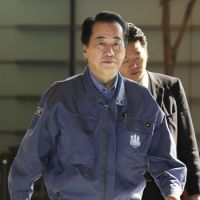 World on his shoulders: Prime Minister Naoto Kan walks into the prime minister's office Friday morning. | KYODO PHOTO