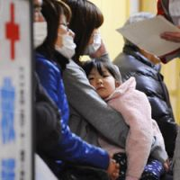 Basic care: A girl sits in her mother's lap Sunday waiting for medical services at a shelter in Rikuzantakata, Iwate Prefecture, which was devastated by the March 11 tsunami. | KYODO PHOTO
