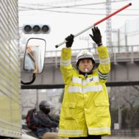Stop sign: A Kanagawa Prefectural Police officer directs traffic at a crossroads in Yokosuka on March 15 after rolling blackouts that day knocked out traffic signals. | KYODO PHOTO