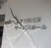 Cracked facade: Cracks run through the wall of the Fukushima No. 1 plant's visitor center. Below: Tetsuo Sakuma loads his pickup with his belongings in the town of Okuma, just a few kilometers from the stricken nuclear plant. | DAVID MCNEILL