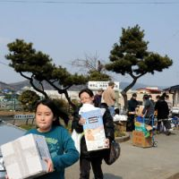 Evacuees carry goods distributed by volunteer groups in Ishinomaki. | SATOKO KAWASAKI PHOTO