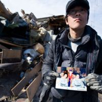 Makoto Takahashi holds a photo of his mother, whom he found dead outside the battered remains of their home in Tona, Miyagi Prefecture, the same day. | ROBERT GILHOOLY PHOTO