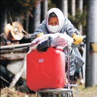 Survival: An elderly woman pushes a cart with a water tank on it Thursday in the town of Yamada, Iwate Prefecture.   KYODO PHOTO