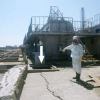 Holed up: A worker at the Fukushima No. 1 nuclear plant points to a cracked storage pit from which highly radioactive water was found leaking Saturday. | KYODO PHOTO