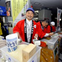 Proof is in the pudding: Fukushima farmer Masaichi Mimura holds a Geiger counter to prove the safety of the prefecture's rice and other fresh produce at an open-air market in Tokyo's Yurakucho district Saturday. | YOSHIAKI MIURA PHOTO