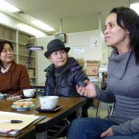 Helping others: Andrea Matsubara (right) speaks with other foreigners at the office of the Miyagi International Association in Sendai on March 23. | KYODO PHOTO