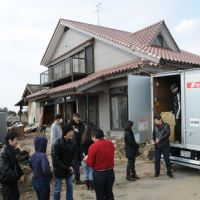 New wardrobe: Volunteers gather outside a house in Arahama, a suburb of Sendai, on March 30. They later distributed donated clothing to survivors of the March 11 disaster. | SATOKO KAWASAKI PHOTO
