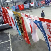 True colors: Fifty 'tairyo bata' banners used to adorn fishing boats are hung out to dry in the backyard of Eiaki Ito in Shiogama, Miyagi Prefecture, on March 30. Ito and his wife, Kazuyo (below), are interviewed in their tsunami-hit fishing equipment shop in Shiogama on March 31. | COURTESY OF EBISUYA, MIZUHO AOKI