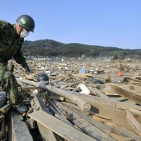 Search still on: A Self-Defense Force member on Sunday searches for people still missing from the March 11 earthquake and tsunami in Rikuzentakata, Iwate Prefecture. About 12,000 SDF members and more than 100 U.S. military personnel were involved in the search on the same day. | KYODO PHOTO