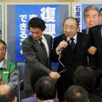 Never left: Re-elected Tokyo Gov. Shintaro Ishihara (left) and his son, Nobuteru, the secretary general of the Liberal Democratic Party (far right), wait for the poll results Sunday at the governor's campaign office in Minato Ward, Tokyo. | KYODO PHOTO
