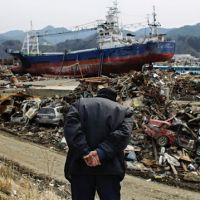 Hasn't gone away: An elderly man observes an area devastated by the giant quake and tsunami in Kesennuma, Miyagi Prefecture, on Monday, exactly a month after the disaster.   AP PHOTO