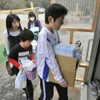 Family shelter: A family moves into temporary housing built for tsunami evacuees in devastated Rikuzentakata, Iwate Prefecture, on Monday.   KYODO PHOTO