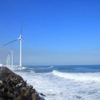 All is calm: Wind-power generators work off a jetty housing power transformers 50 meters off Kamisu, Ibaraki Prefecture, in this photo taken before the March 11 tsunami. | COURTESY OF MITANI CORP.