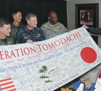 Senior personnel from the U.S. Navy, Marines, and Army present Defense Minister Toshimi Kitazawa (right) an Operation Tomodachi banner in a wardroom aboard the aircraft carrier USS Ronald Reagan on April 4. | US NAVY