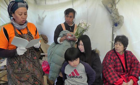 Healing spirit: Syafwina (left), an Indonesian whose home was destroyed in the 2004 tsunami that hit Aceh on Sumatra, reads a poem she wrote about the tragedy to evacuees at Minamisanriku, Miyagi Prefecture, on Saturday.   KYODO PHOTO