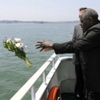 Special significance: Cardinal Robert Sarah throws flowers into the ocean during prayers for victims of the March 11 earthquake and tsunami as he rides on a sightseeing boat in Matsushima Bay, Miyagi Prefecture, on Monday.   KYODO PHOTO