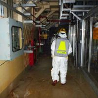 Dressed for work: A worker enters the No. 2 reactor building at Fukushima No. 1 nuclear power plant on Wednesday.   KYODO PHOTO