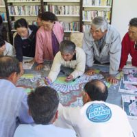Planning pays off: Residents at Nonoshima Island in Miyagi Prefecture gather to draw up a disaster prevention map in August 2008. | KYODO PHOTO