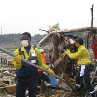 Making a difference: Volunteers, including refugees and both Japanese and foreign exchange students, work hard removing debris in Rikuzentakata, Iwate Prefecture, earlier this month. | COURTESY OF JAPAN ASSOCIATION FOR REFUGEES
