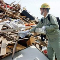 Testing work: A worker on May 9 gauges the radiation level of debris from the Tohoku disaster at Iwaki, Fukushima Prefecture, which is located near the crippled Fukushima No. 1 nuclear plant. | KYODO PHOTO
