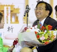 Flower power: Aomori Gov. Shingo Mimura receives flowers at his electoral headquarters Sunday as exit polls showed he would be re-elected in the gubernatorial election. | KYODO