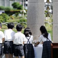 Alive in memory: Children place flowers Tuesday at an altar to mark the 10th anniversary of the fatal stabbings of eight children at Ikeda Elementary School in Ikeda, Osaka Prefecture.   KYODO