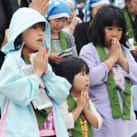 A time to remember, a time to protest: Children in Ishinomaki, Miyagi Prefecture, mark the three-month anniversary of the March 11 disasters Saturday by praying for the victims, while a panoramic photo of Ozuchi, Iwate Prefecture, shows the scale of devastation. | KYODO PHOTO