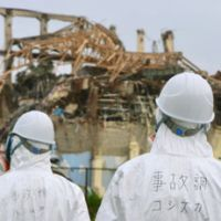Where'd it go?: Members of the panel investigating the nuclear crisis at the Fukushima No. 1 power plant gaze at its No. 3 reactor on Friday. | KYODO PHOTO