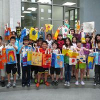 Lucky bags: Fifth-graders at Osaka International School of Kwansei Gakuin in Minoo, Osaka Prefecture, show off bags painted by students from around the world.