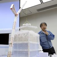 Under a lid: Junichi Matsumoto, a spokesman for Tokyo Electric Power Co., uses a model Monday to explain Tepco's plan for building giant covers to contain radiation from the Fukushima No. 1 nuclear power plant. | KYODO PHOTO