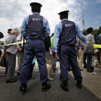 Fallout: Police guide shareholders arriving for Tokyo Electric Power Co.'s investors' meeting Tuesday in Tokyo.   AP