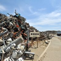 Waste not, want not: Utility poles and other wreckage from the March quake and tsunami are piled up in front of a sign reading 'Metal waste storage area' at a temporary disposal site in Rikuzentakata, Iwate Prefecture, in late May. | YOSHIAKI MIURA