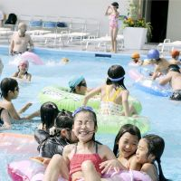 Young having fun: Children bathe in a swimming pool at a Tokyo hotel on July 2. | KYODO PHOTO