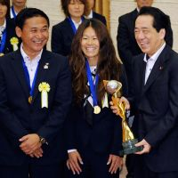 Getting his kicks: Prime Minister Naoto Kan holds the Women's World Cup trophy alongside national soccer team captain Homare Sawa and head coach Norio Sasaki at Kan's official residence Tuesday. | AP