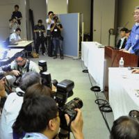 Road to recovery?: Tokyo Electric Power Co. President Toshio Nishizawa (standing) faces the media Tuesday evening at the company headquarters in Tokyo as he announces the utility's updated road map to contain the nuclear crisis at its Fukushima No. 1 plant. | KYODO